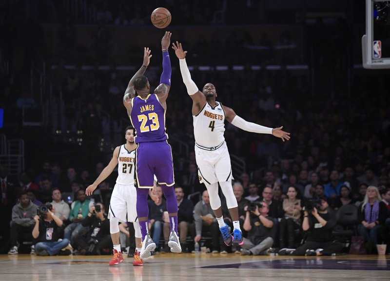 Los Angeles Lakers forward LeBron James (23) shoots as Denver Nuggets forward Paul Millsap, right, defends while guard Jamal Murray watches during the first half of an NBA basketball game Wednesday, March 6, 2019, in Los Angeles. (AP Photo/Mark J. Terrill)