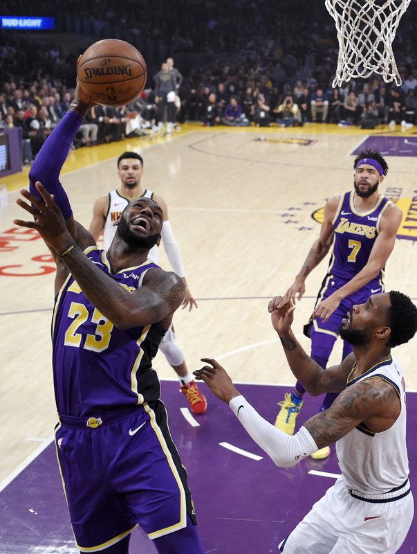 Los Angeles Lakers forward LeBron James, left, shoots as Denver Nuggets guard Will Barton defends during the first half of an NBA basketball game Wednesday, March 6, 2019, in Los Angeles. (AP Photo/Mark J. Terrill)