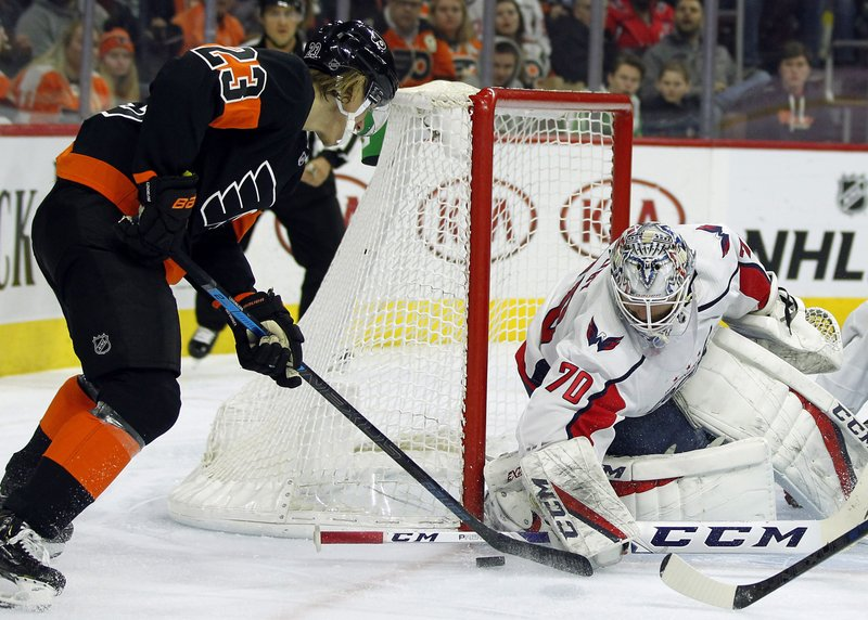 Philadelphia Flyers' Oskar Lindblom, left, digs at the puck blocked by Washington Capitals' Braden Holtby during the second period of an NHL hockey game Wednesday, March 6, 2019, in Philadelphia. (AP Photo/Tom Mihalek)