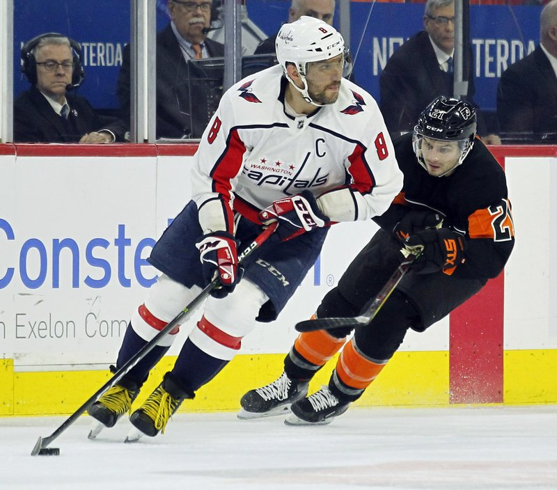 Washington Capitals' Alex Ovechkin, front, controls the puck while followed by Philadelphia Flyers' Scott Laughton during the second period of an NHL hockey game Wednesday, March 6, 2019, in Philadelphia. (AP Photo/Tom Mihalek)