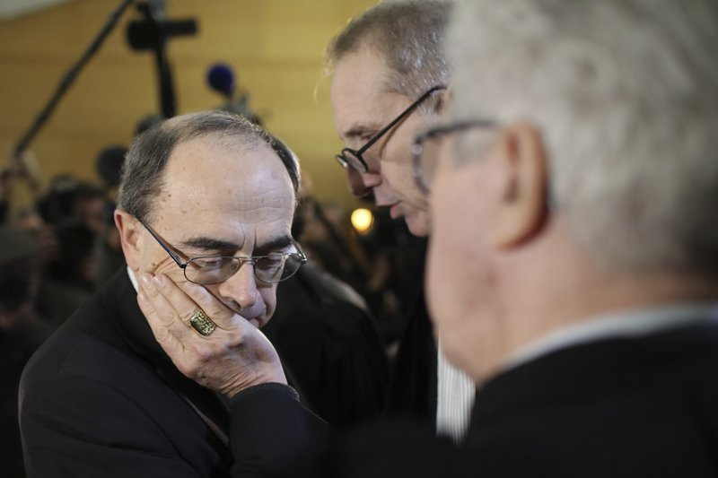 FILE - In this Jan.7, 2019 file photo, Cardinal Philippe Barbarin listens to his lawyers, Jean-Felix Luciani, 2nd right, and Andre Soulier, back to camera, as he attends the start his trial, in Lyon, central France. (AP Photo/Laurent Cipriani, File)