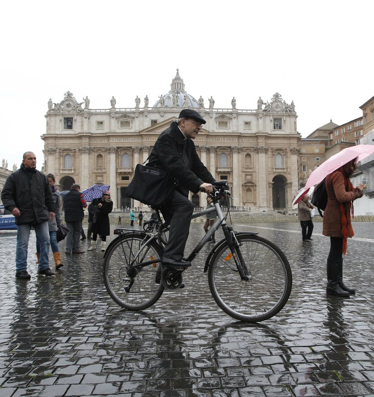 FILE - In this Friday, March 8, 2013 file photo, French Cardinal Philippe Barbarin rides his bicycle in St. (AP Photo/Alessandra Tarantino, File )