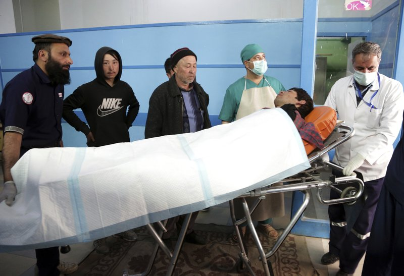 Afghans carry an injured man at a hospital in Kabul, Afghanistan, Thursday, March 7, 2019. Afghan officials say several explosions have struck outside a ceremony in Kabul attended by the country's chief executive and the former president, both of whom were unharmed. (AP Photo/Rahmat Gul)