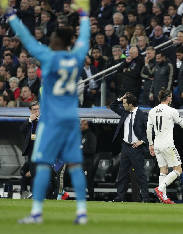 Real coach Santiago Solari reacts as Ajax goalkeeper Andre Onana celebrates their side's 3rd goal, during the Champions League soccer match between Real Madrid and Ajax at the Santiago Bernabeu stadium in Madrid, Spain, Tuesday, March 5, 2019. (AP Photo/Manu Fernandez)