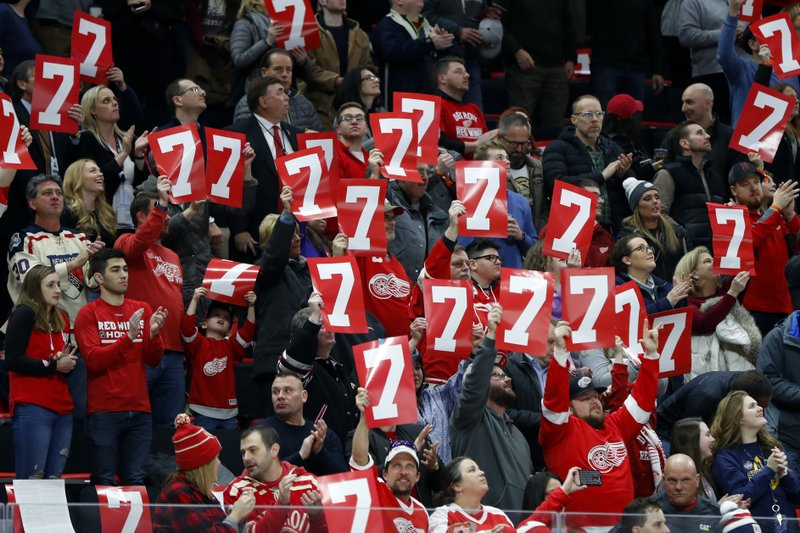 Detroit Red Wings fans hold up the No. 7 in honor of former player Ted Lindsay, who died Monday, during a moment to honor Lindsay during the first period of the team's NHL hockey game against the New York Rangers, Thursday, March 7, 2019, in Detroit. (AP Photo/Paul Sancya)