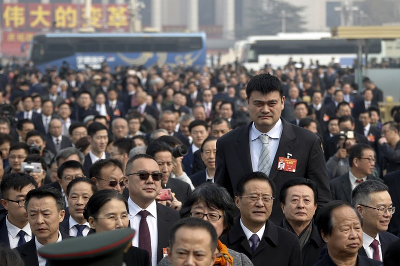 In this March 3, 2019, photo, former NBA basketball player Yao Ming, left, a delegate to the Chinese People's Political Consultative Conference (CPPCC), towers over other delegates as they arrive at the Great Hall of the People to attend the opening session of the CPPCC in Beijing. (AP Photo/Andy Wong, File)