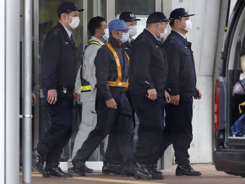In this March 6, 2019, photo, former Nissan Chairman Carlos Ghosn, walks out with security guards from Tokyo Detention Center in Tokyo, after posting 1 billion yen ($8. (AP Photo/Eugene Hoshiko, File)