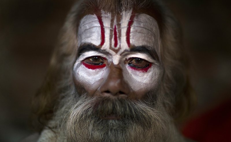 In this March 4, 2019, photo, a Hindu holy man poses for a photograph as he smears his face with ash and vermilion powder at the courtyard of the Pashupatinath Temple during Shivaratri festival in Kathmandu, Nepal. (AP Photo/Niranjan Shrestha, File)