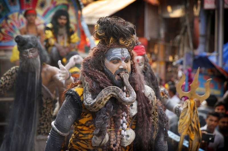 In this March 4, 2019, photo, a devotee dressed as Lord Shiva puts a snake in his mouth during a procession to mark Mahashivratri festival in Prayagraj, Uttar Pradesh state, India. (AP Photo/ Rajesh Kumar Singh, File)