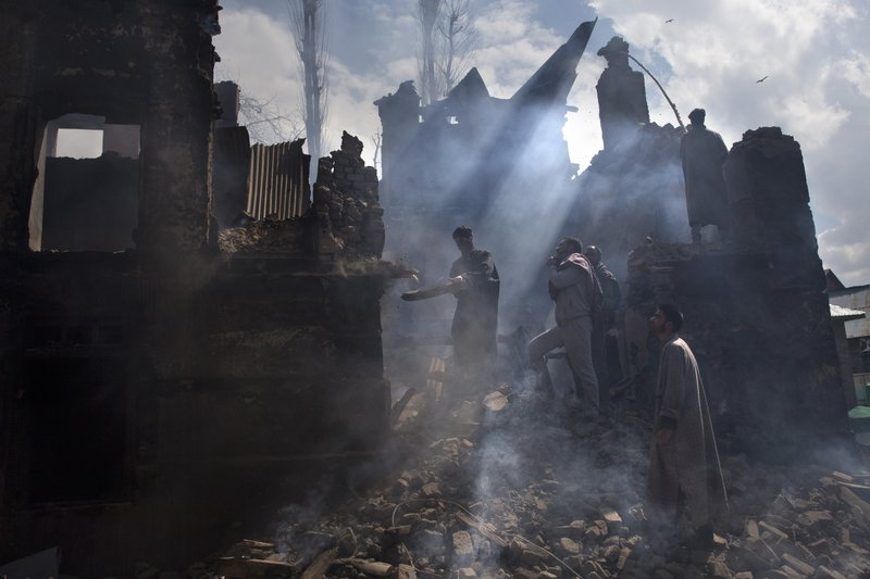 In this March 4, 2019, photo, Kashmiri men dismantle a portion of a house destroyed in a gunbattle in Tral village, south of Srinagar, Indian controlled Kashmir. (AP Photo/ Dar Yasin, File)