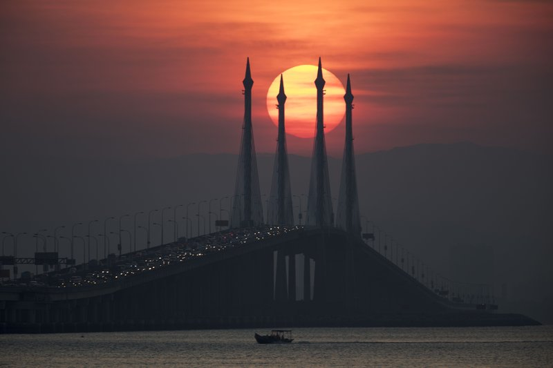 In this March 7, 2019, photo, the sun rises over the Penang bridge in Penang island, Northern Malaysia. (AP Photo/Vincent Thian, File)