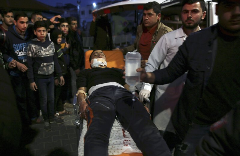 Medics wheel a wounded teenager, who was shot by Israeli troops during a protest at the Gaza Strip's border with Israel, into the treatment room of Shifa hospital in Gaza City, Friday, March 8, 2019. (AP Photo/Adel Hana)