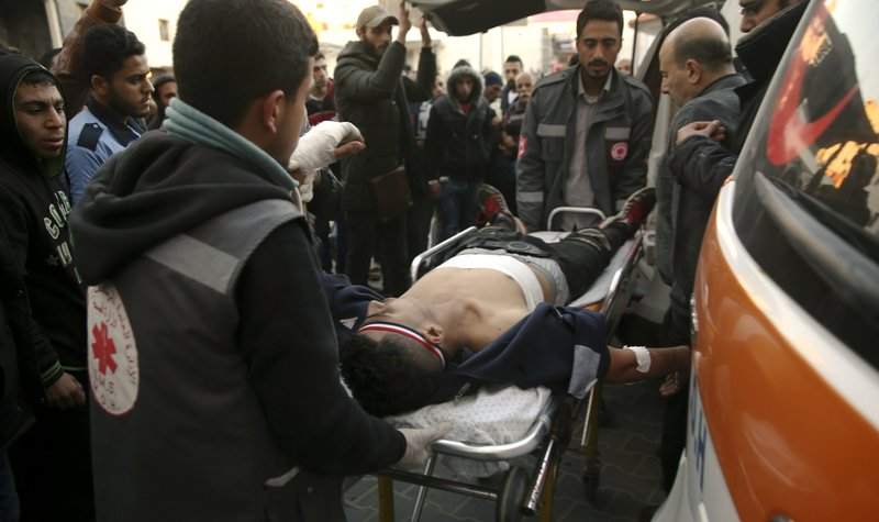 Medics move a wounded youth, who was shot by Israeli troops during a protest at the Gaza Strip's border with Israel, into the treatment room of Shifa hospital in Gaza City, Friday, March 8, 2019. (AP Photo/Adel Hana)