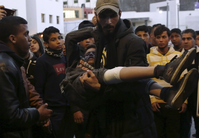 A man helps a wounded youth, who was shot by Israeli troops during a protest at the Gaza Strip's border with Israel, into the treatment room of Shifa hospital in Gaza City, Friday, March 8, 2019. (AP Photo/Adel Hana)
