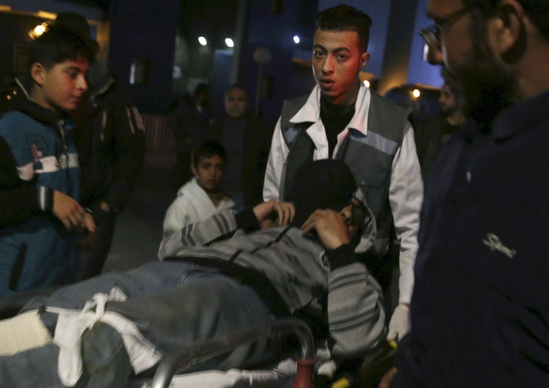 Teenagers watch medics while move a wounded man, who was shot by Israeli troops during a protest at the Gaza Strip's border with Israel, into the treatment room of Shifa hospital in Gaza City, Friday, March 8, 2019. (AP Photo/Adel Hana)