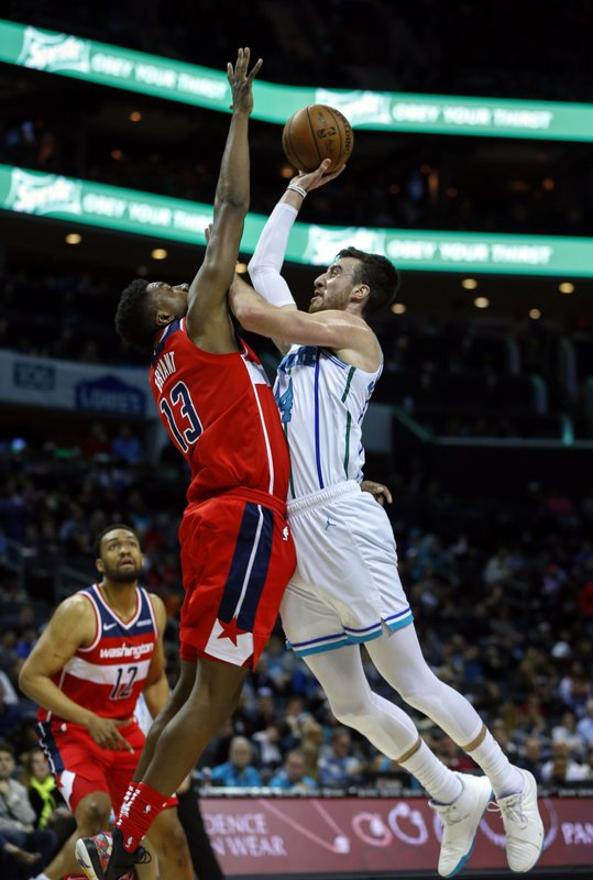 Charlotte Hornets forward Frank Kaminsky, right, shoots over Washington Wizards center Thomas Bryant (13) in the first half of an NBA basketball game in Charlotte, N. (AP Photo/Nell Redmond)