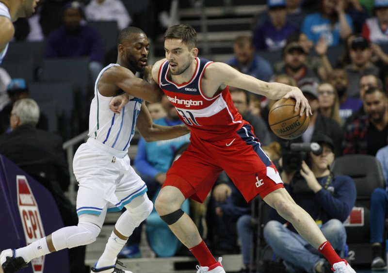 Washington Wizards guard Tomas Satoransky, right, drives into Charlotte Hornets guard Kemba Walker in the first half of an NBA basketball game in Charlotte, N. (AP Photo/Nell Redmond)