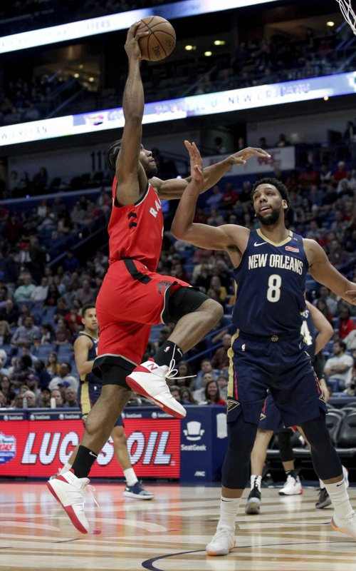 Toronto Raptors forward Kawhi Leonard, left, scores over New Orleans Pelicans center Jahlil Okafor (8) in the first half of an NBA basketball game in New Orleans, Friday, March 8, 2019. (AP Photo/Scott Threlkeld)