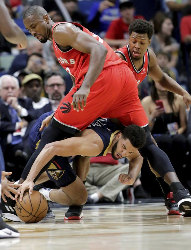 New Orleans Pelicans guard Kenrich Williams (34) goes under Toronto Raptors center Serge Ibaka (9) to grab the ball in the second half of an NBA basketball game in New Orleans, Friday, March 8, 2019. (AP Photo/Scott Threlkeld)