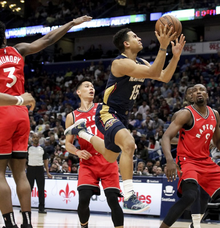 New Orleans Pelicans guard Frank Jackson (15) drives to the basket against Toronto Raptors guard Jeremy Lin (17) and center Serge Ibaka (9) in the second half of an NBA basketball game in New Orleans, Friday, March 8, 2019. (AP Photo/Scott Threlkeld)