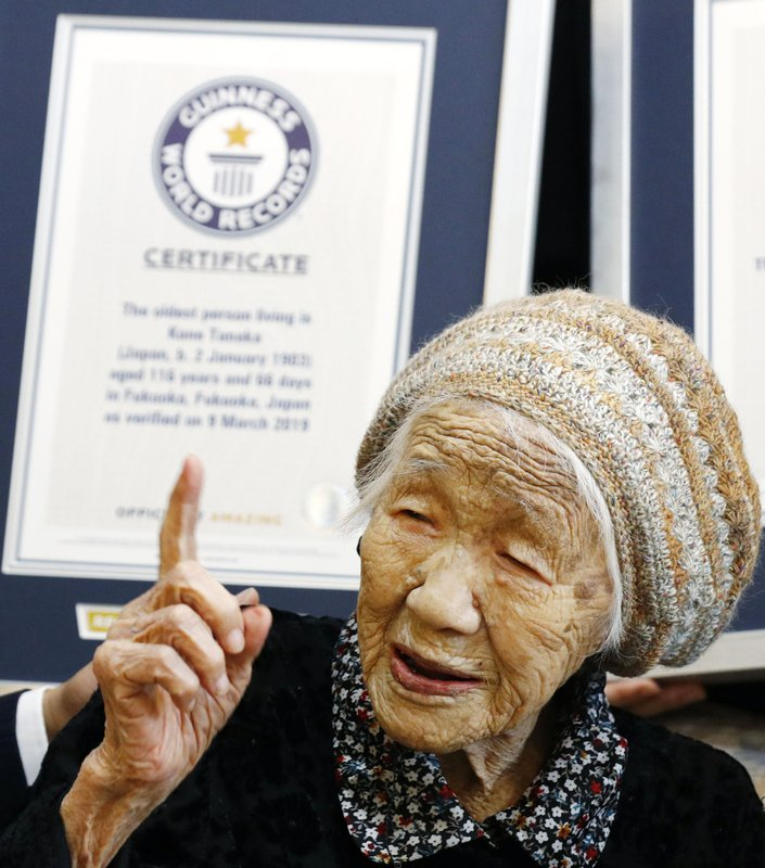 Kane Tanaka, a 116-year-old Japanese woman, gestures after receiving a Guinness World Records certificate, back, at a nursing home where she lives in Fukuoka, southwestern Japan, Saturday, March 9, 2019. (Takuto Kaneko/Kyodo News via AP)