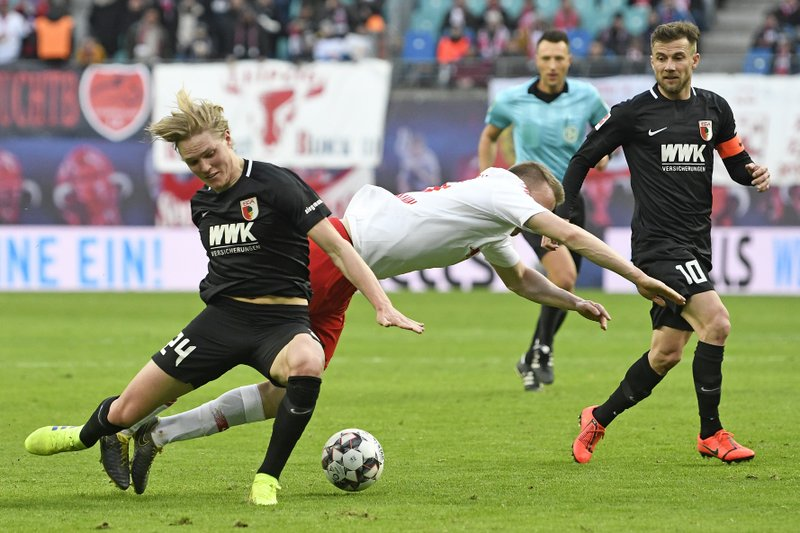 Augsburg's Kevin Danso, left, challenges for the ball against Leipzig's Lukas Klostermann, right, during the German first division Bundesliga soccer match between RB Leipzig and FC Augsburg in Leipzig, Germany, Saturday, March 9, 2019. (AP Photo/Jens Meyer)