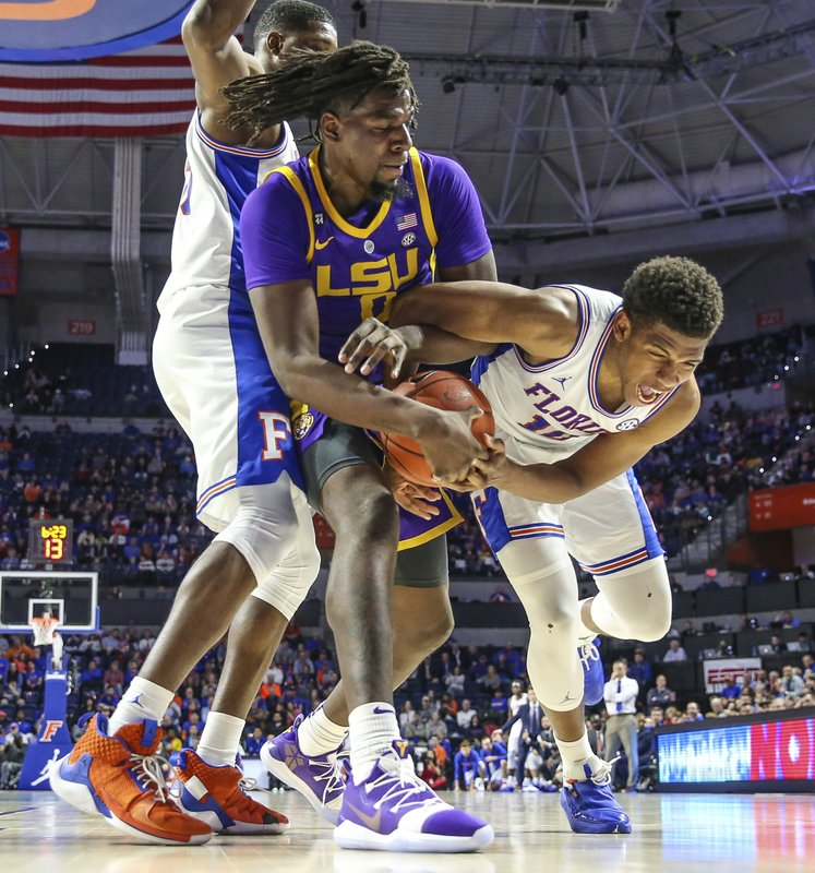 LSU forward Naz Reid (0) and Florida forward Keyontae Johnson (11) vie for possession of the ball during the second half of an NCAA college basketball game in Gainesville, Fla. (AP Photo/Gary McCullough)