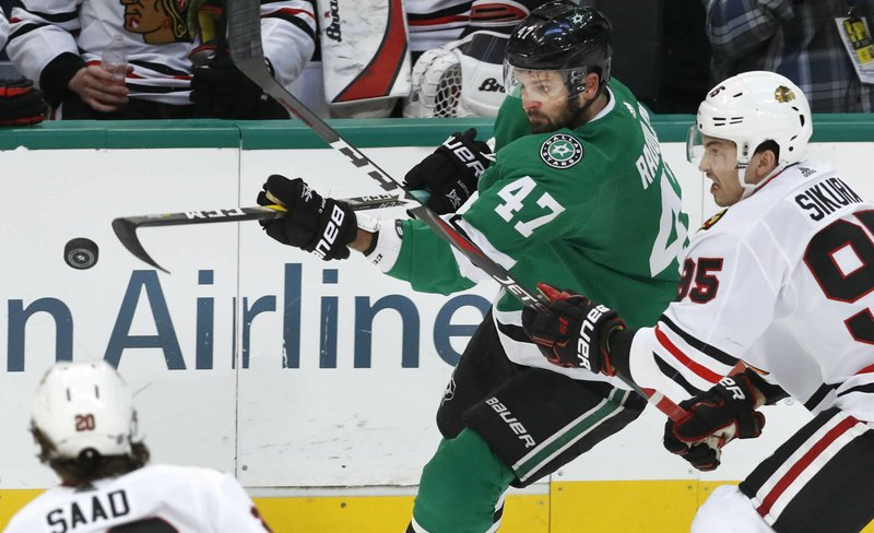 Dallas Stars right wing Alexander Radulov (47) and Chicago Blackhawks right wing Dylan Sikura (95) reach for the puck during the second period of an NHL hockey game in Dallas, Saturday, March 9, 2019. (AP Photo/LM Otero)