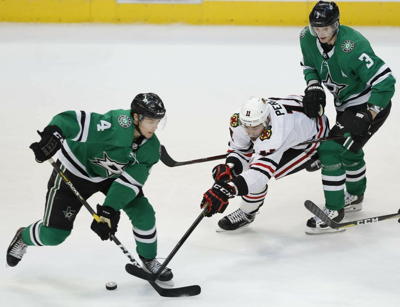 Chicago Blackhawks left wing Brendan Perlini (11) reaches for the puck against Dallas Stars defensemen Miro Heiskanen (4) and John Klingberg (3) during the second period of an NHL hockey game in Dallas, Saturday, March 9, 2019. (AP Photo/LM Otero)