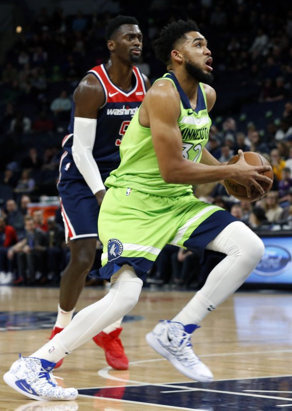 Minnesota Timberwolves' Karl-Anthony Towns, right, drives past Washington Wizards' Bobby Portis in the first half of an NBA basketball game Saturday, March 9, 2019, in Minneapolis. (AP Photo/Jim Mone)