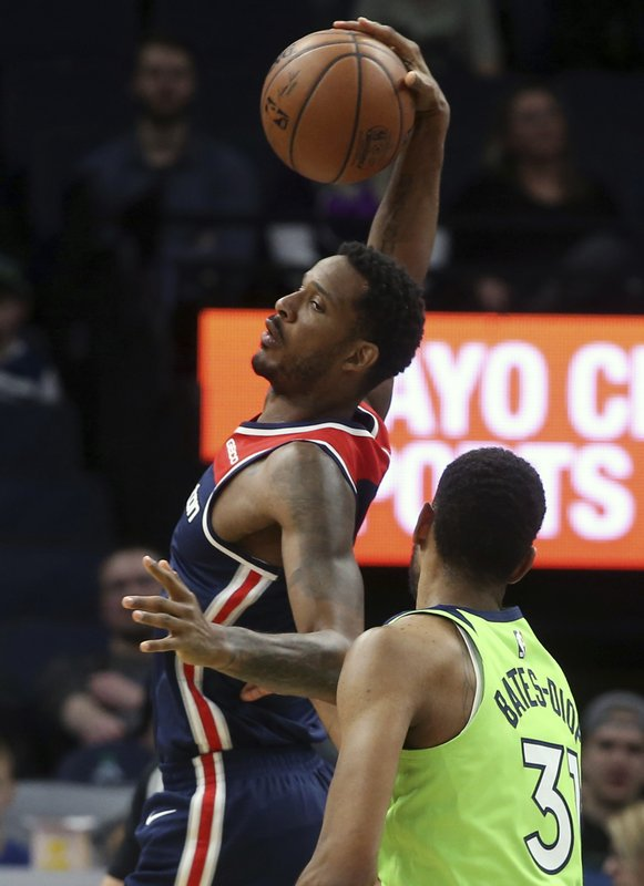 Washington Wizards' Trevor Ariza, left, pulls in a pass as Minnesota Timberwolves' Keita Bates-Diop defends in the first half of an NBA basketball game Saturday, March 9, 2019, in Minneapolis. (AP Photo/Jim Mone)