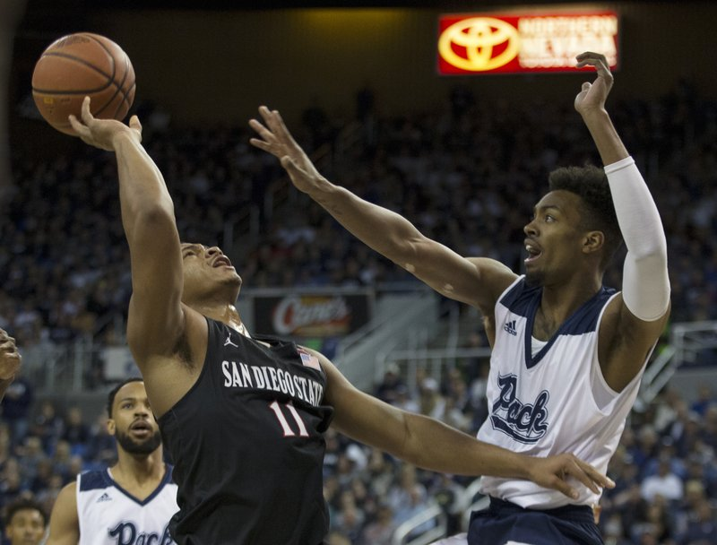 San Diego State forward Matt Mitchell (11) is fouled by Nevada forward Jordan Brown (21) in the first half of an NCAA college basketball game in Reno, Nev. (AP Photo/Tom R. Smedes)