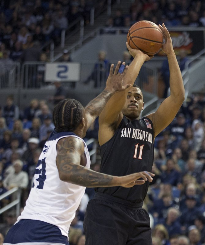 San Diego State forward Matt Mitchell (11) shoots over Nevada forward Jordan Caroline (24) in the first half of an NCAA college basketball game in Reno, Nev. (AP Photo/Tom R. Smedes)