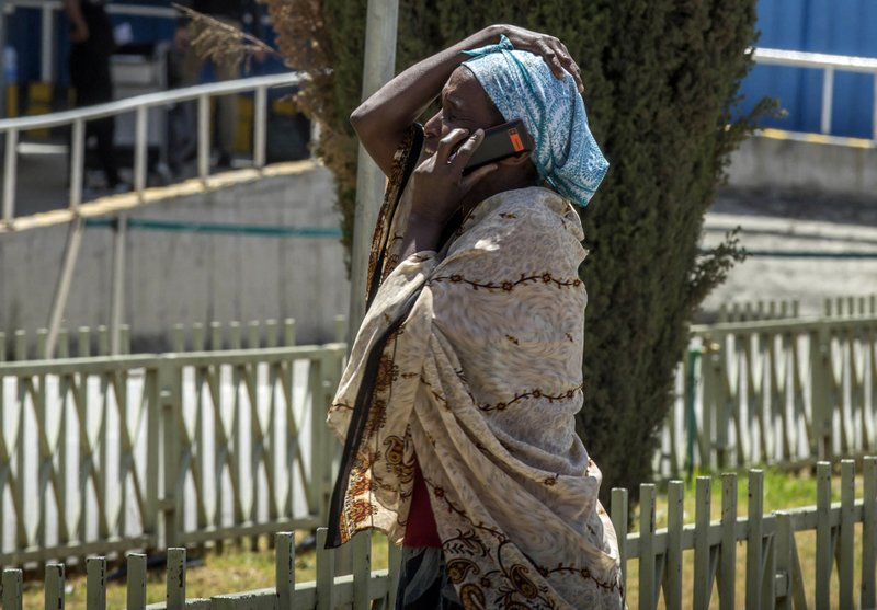 A family member of a victim involved in a plane crash talks on a mobile phone at Addis Ababa international airport Sunday, March 10, 2019. (AP Photo/Mulugeta Ayene)