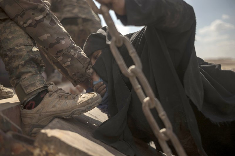 In this Wednesday, March 6, 2019, photo, a woman kisses the hand of a soldier at a reception area for people evacuated from the last shred of territory held by Islamic State militants, outside Baghouz, Syria. (AP Photo/Gabriel Chaim)
