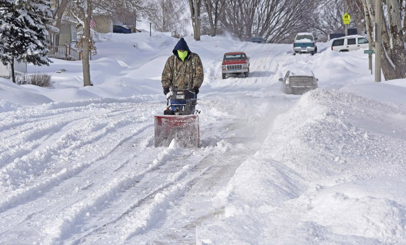 Randy Ohlhauser clears snow from the street next to his home on Saturday, March 9, 2019, in Bismarck, N. (Tom Stromme/The Bismarck Tribune via AP)