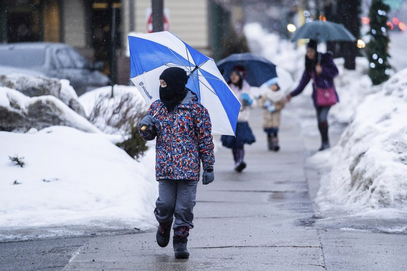 Ten-year-old Connor Chan made his way in the rain down Hennepin Avenue in Minneapolis, Saturday, March 9, 2019. (Mark Vancleave/Star Tribune via AP)