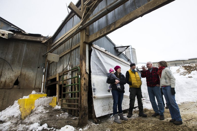 Minnesota Gov. Tim Walz, second from right, and U.S. Sen. Tina Smith, right, talk with Katie and Rob Kreidermacher while looking at a damaged barn during a visit to the Kreidermacher's farm, Saturday, March 9, 2019, near Altura, Minn. (Andrew Link/The Rochester Post-Bulletin via AP)