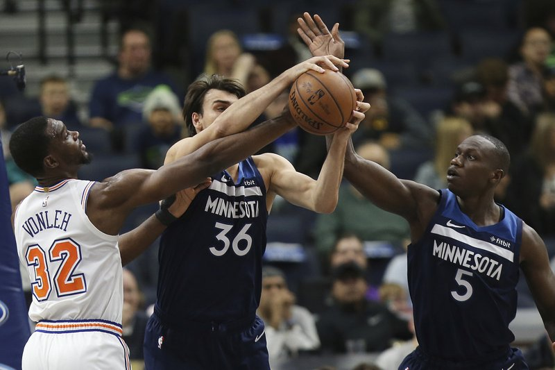Minnesota Timberwolves' Dario Saric (36) and Minnesota Gorgui Dieng (5) go for a rebound ball against New York Knicks' Noah Vonleh (32) in the first half of an NBA basketball game Sunday, March 10, 2019, in Minneapolis. (AP Photo/Stacy Bengs)