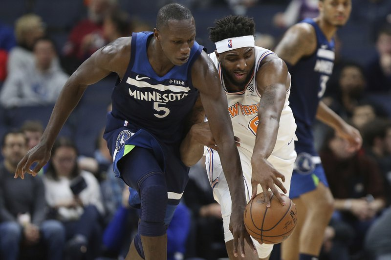 Minnesota Timberwolves' Gorgui Dieng, left, and New York Knicks' Mitchell Robinson go after a loose ball in the first half of an NBA basketball game Sunday, March 10, 2019, in Minneapolis. (AP Photo/Stacy Bengs)