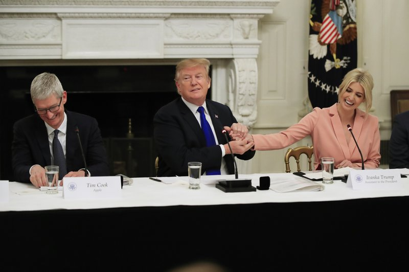 American Workforce Policy Advisory Board co-chair Ivanka Trump, right, and Apple Inc. CEO Tim Cook, left, react as President Donald Trump thank his daughter during the advisory board's first meeting in the State Dining Room of the White House in Washington, Wednesday, March 6, 2019. (AP Photo/Manuel Balce Ceneta)