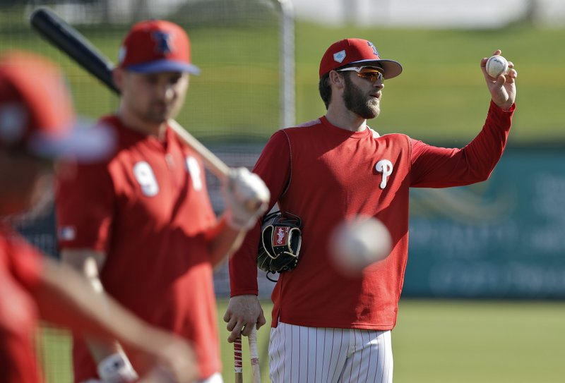 Philadelphia Phillies' Bryce Harper, right, holds up a baseball after taking batting practice before a spring training baseball game against the Tampa Bay Rays Monday, March 11, 2019, in Clearwater, Fla. (AP Photo/Chris O'Meara)