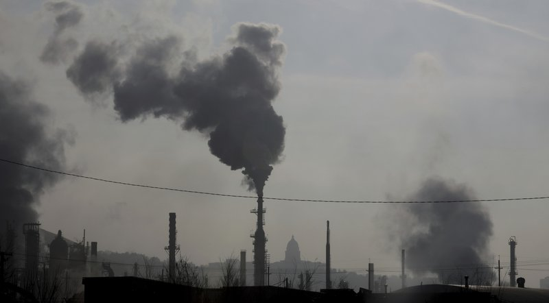 FILE - In this Dec. 10, 2018 photo, smokestacks near an oil refinery are seen in front of the Utah State Capitol as an inversion settles over Salt Lake City. (AP Photo/Rick Bowmer, File)