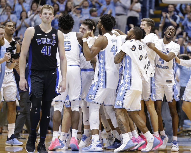 North Carolina players celebrate while Duke's Jack White (41) walks away following an NCAA college basketball game in Chapel Hill, N. (AP Photo/Gerry Broome)