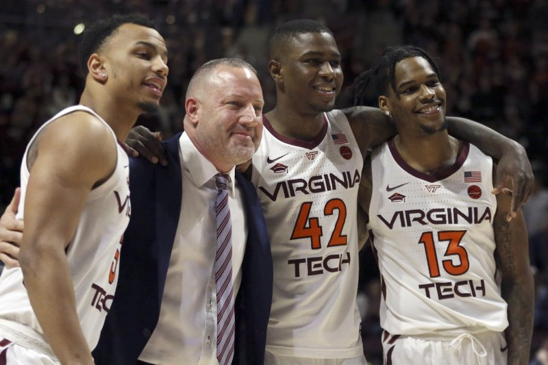 Virginia Tech coach Buzz Williams poses for a photograph with seniors Justin Robinson, Ty Outlaw (42) and Ahmed Hill (13) before the team's NCAA college basketball game against Miami in Blacksburg, Va. (Matt Gentry/The Roanoke Times via AP)