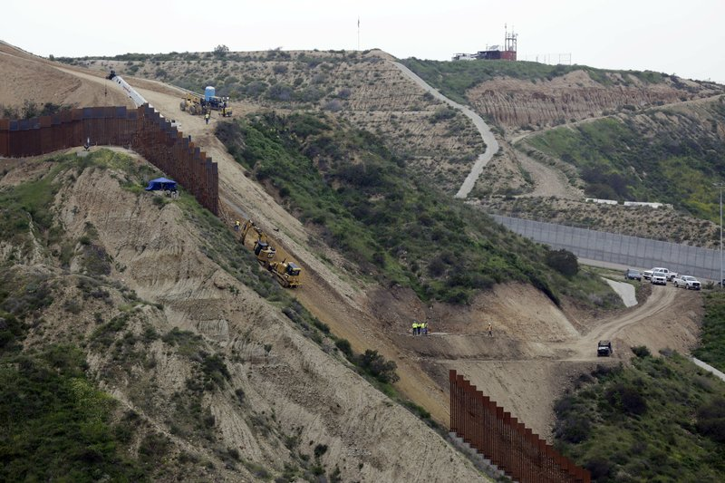 Construction crews replace a section of the primary wall separating San Diego, above right, and Tijuana, Mexico, below left, Monday, March 11, 2019, seen from Tijuana, Mexico. (AP Photo/Gregory Bull)