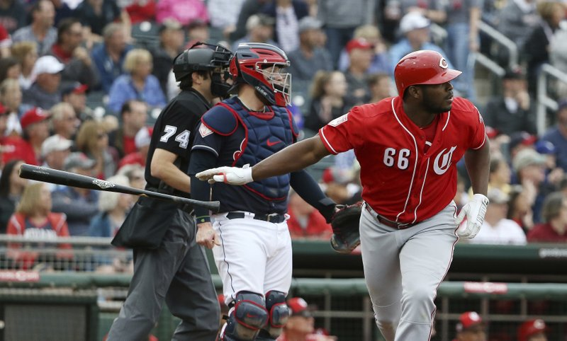 Cincinnati Reds right fielder Yasiel Puig (66) tosses his bat as he watches the flight of his home run while Cleveland Indians catcher Roberto Perez, center, and umpire John Tumpane (74) look on during the third inning of a spring training baseball game Monday, March 11, 2019, in Goodyear, Ariz. (AP Photo/Ross D. Franklin)