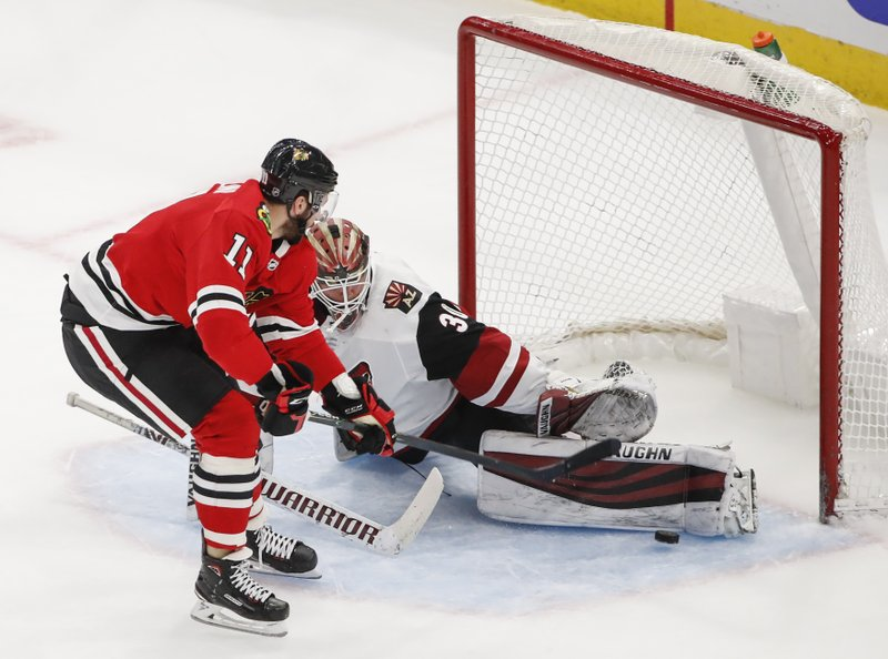 Arizona Coyotes goaltender Calvin Pickard (30) defends against Chicago Blackhawks left wing Brendan Perlini (11) during the second period of an NHL hockey game Monday, March 11, 2019, in Chicago. (AP Photo/Kamil Krzaczynski)