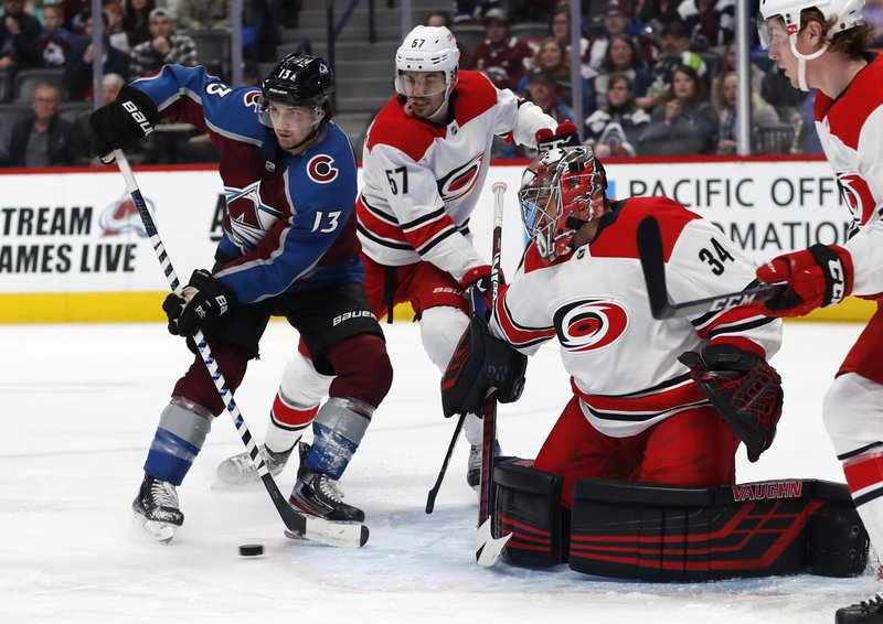 Colorado Avalanche center Alexander Kerfoot, left, tries to direct the puck as Carolina Hurricanes defenseman Trevor van Riemsdyk, center, and goaltender Petr Mrazek defend the net in the first period of an NHL hockey game Monday, March 11, 2019, in Denver. (AP Photo/David Zalubowski)