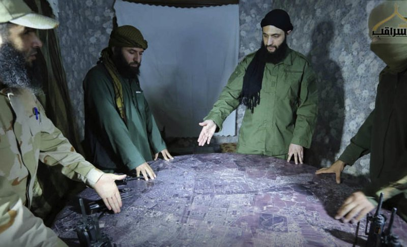 FILE - This undated file photo released by a militant group in 2016, shows Abu Mohammed al-Golani of the militant Levant Liberation Committee and the leader of Syria's al-Qaida affiliate, second right, discussing battlefield details with field commanders over a map, in Aleppo, Syria. (Militant UGC via AP, File)